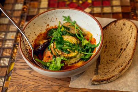 Bowl with baked eggplants, tomatoes, arugula leaves on table. Piece of rye bread. Vegan and diet concept