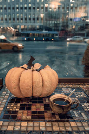 Holiday symbol, decor, halloween natural pumpkin with carved paper black bats and cup of coffee, twilight, street window view