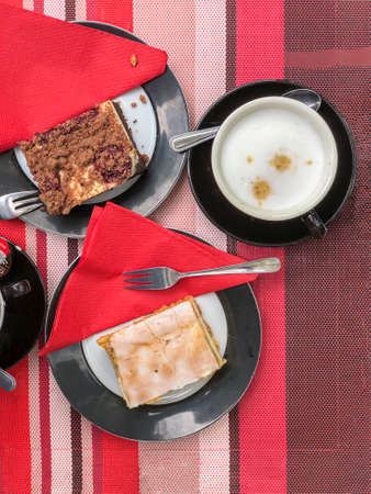 Top view of table, cakes and coffee cup, red napkins, flat lay Standard-Bild
