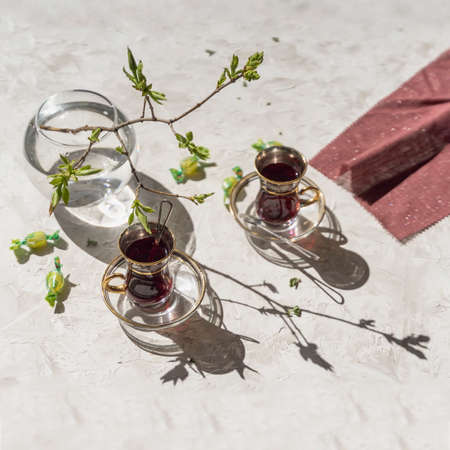 Spring sunny morning, cups with fruit tea, napkin and young tender tree branches, openwork shadows on the table Standard-Bild