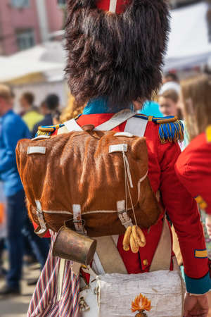 Young man back to us in folk dress and fluffy hat with backpack, cheerful national costume on celebration Standard-Bild