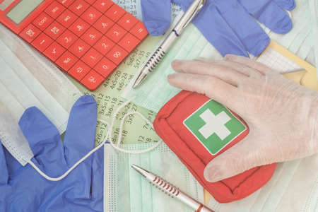 Hand in a medical glove with first aid kit, pens, calculator, medical masks on school notebook. Disease prevention concept. Concept of Stay safe Standard-Bild
