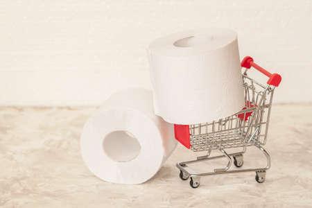 Big rolls of toilet paper in little trolley, mini cart. Consumer essential goods, hygiene, diarrhea, antipanic concepts