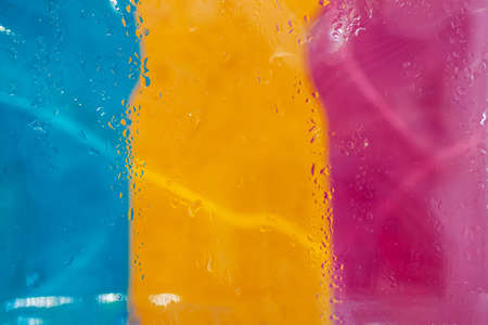Abstract picturesque blurred tricolor with raindrops on glass, neon lights. Modern vivid background