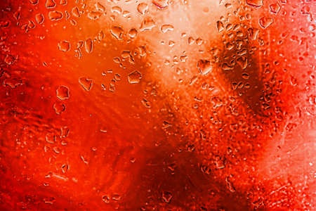 Abstract red background with blurred raindrops on glass, illuminated neon lights. Modern vivid background