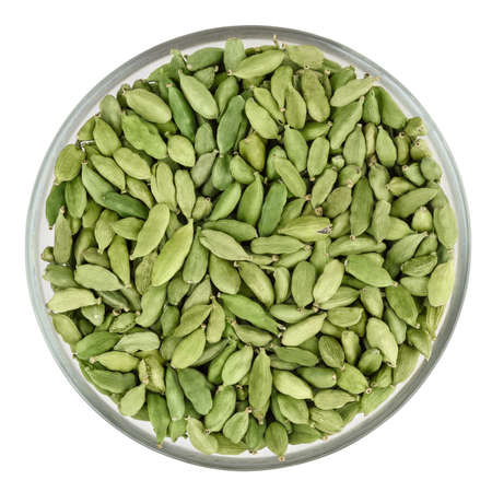 Green cardamon pods in glass bowl isolated on white background with clipping path