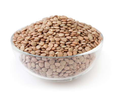 Uncooked lentils in glass bowl isolated on white background with clipping path