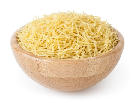 Uncooked vermicelli pasta in wooden bowl isolated on white