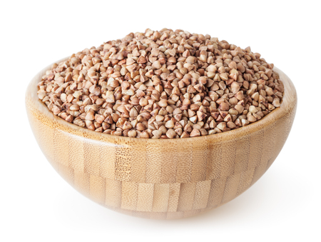 Roasted buckwheat grains in wooden bowl isolated on white