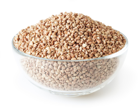 Roasted buckwheat grains in glass bowl isolated on white background