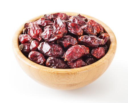 Dried wild rose berries in wooden bowl isolated on white background