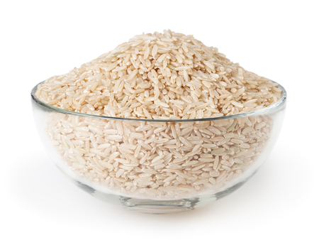 Uncooked brown rice in glass bowl isolated on white background