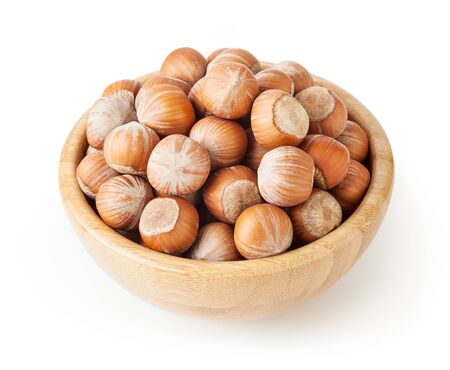 Hazelnuts in wooden bowl isolated on white background