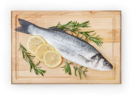 Fresh uncooked seabass with lemon and rosemary on wooden board over white backdground with clipping path