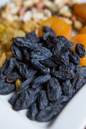 Blue large raisins. Large white plate with nuts raisins and dried fruits.