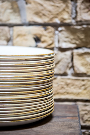 Stacks of cleaned white plates for catering buffet in restaurant room.