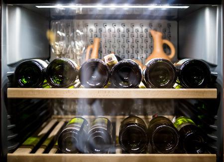Wine bottles cooling in refrigerator.