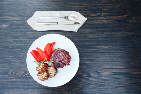 Grilled meat with eggplant and red pepper on a white plate. Grilled meat with vegetables on a white plate. wooden background.