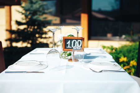 Table setting in a restaurant on the summer terrace.  Tablet on the table one hundred.