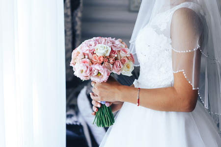 Bride stands at the window and holds a wedding bouquet. Close-up. 스톡 콘텐츠