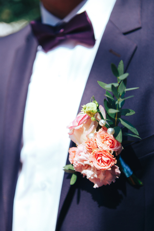 elegant groom dressed in purple suit and white shirt. wedding decor on a jacket. 版權商用圖片