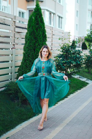 Young woman in green dress outdoors. Modern dress in ethnic style.