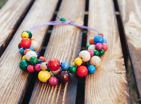 Multicolor beads handmade. Wooden background. Ukrainian style.