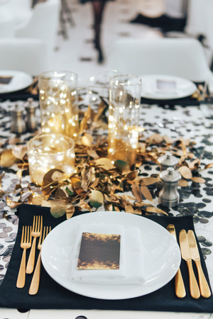 Dinner tableis decorated in black and gold. Garland in a glass flask. Wedding decorations