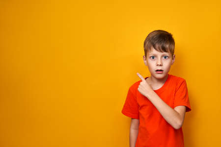 Child schoolboy with a surprised face in an orange t-shirt on an isolated yellow background with hand points to the place for text, expressing emotions