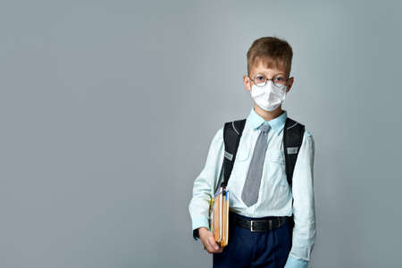 Schoolboy pupil wearing medical mask during virus and flu outbreak, illness protection for kids. Cute boy breathes through mask on gray isolated background, back to school.