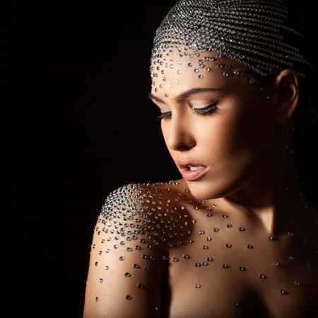 Woman with art design on the body and face, studded with rhinestones. photo