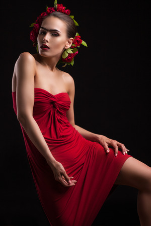 spaniard: young woman in a red dress with flowers on the head, shot on a black background Stock Photo