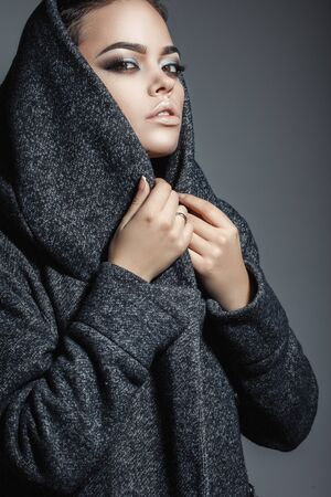 rigor: young woman in a gray coat with a hood pulled over his head