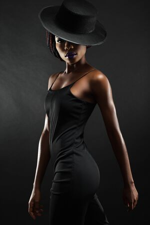 dark skinned: dark skinned woman on a black background with a fashionable hat on his head