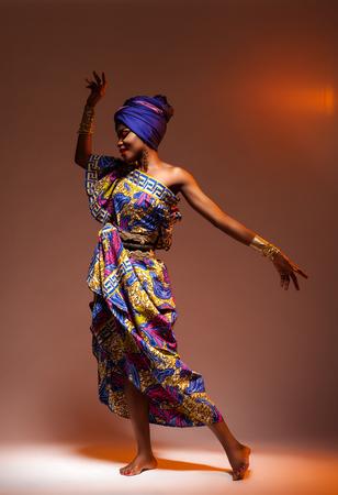 Dance hot African night, a beautiful woman in a bright dress