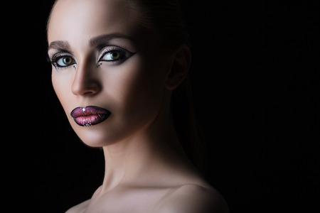 austere: austere and beautiful young woman coming out of the darkness