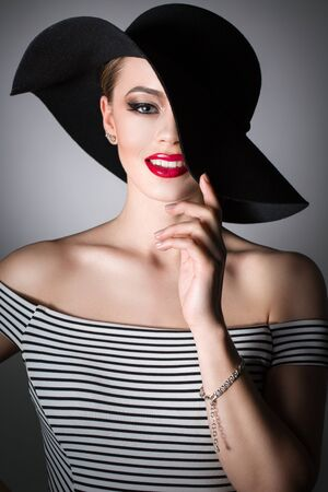 Portrait of a young girl in a black hat on a dark background Stock Photo