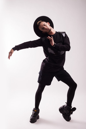 dancing young man in black clothes on a light background Stock Photo