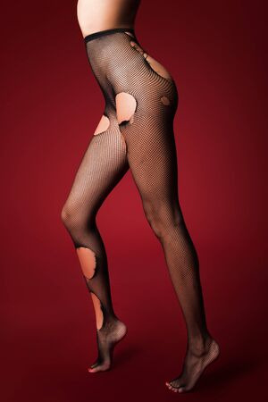torn stockings: slender legs in the torn stockings on red background