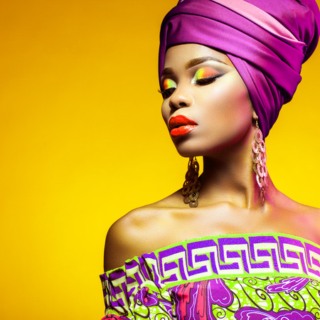 African woman in a bright dress on orange background Stock Photo