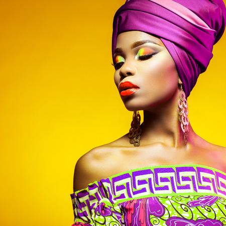 African woman in a bright dress on orange background Foto de archivo
