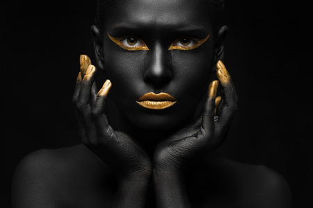 black background and black woman with chic gold makeup