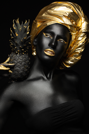 black woman with black pineapple in her hands, gorgeous image of black and zloty Foto de archivo