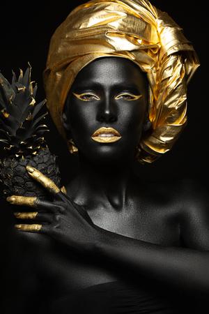 schwarze Frau mit schwarzer Ananas in den Händen, wunderschönes Bild von Schwarz und Zloty