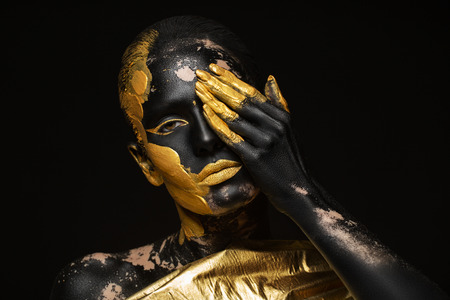 portrait of a beautiful and young woman with gold paint on her body