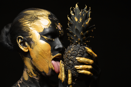 black woman with black pineapple in her hands, gorgeous image of black and zloty 版權商用圖片
