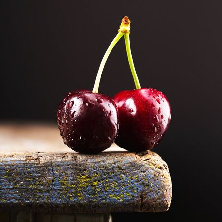 two cherries on the edge of the table, sweet and ripe berry