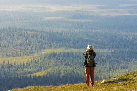 Young woman on a top of hill in Lapland, Finland