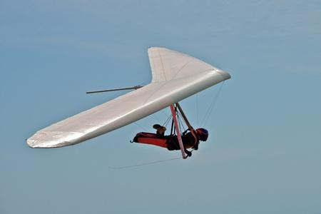 parapente: Cuelgan a hombre desliz�ndose sobre un ala blanca con cielo en segundo plano