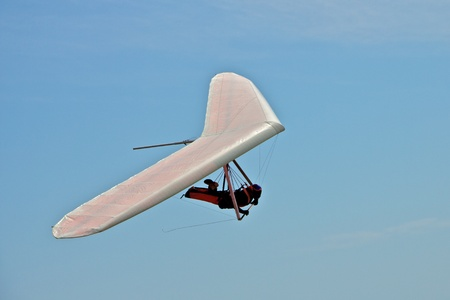 Hang gliding man on a white wing with sky in the background Фото со стока